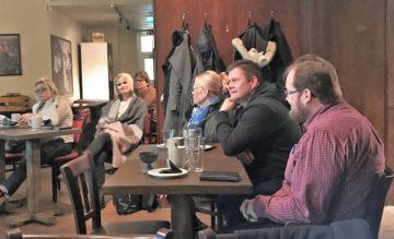 Verkkokauppaklubin osanottajia keskustelemassa verkkokauppojen kehittämisestä kahvilan pöytien ääressä.