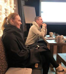 Emmi Liikanen istuu etualalla kahvilapöydässä ja Jukka Kumpusalo taustalla. He katsovat ulos kuvasta ja hymyilevät.