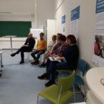 Ihmiset rivissä luokan seinustalla kuuntelemassa seminaariesityksiä.