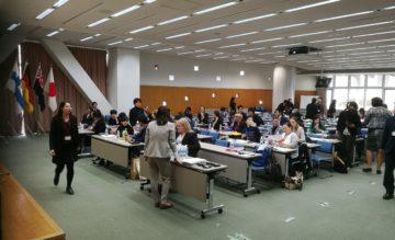 Ihmiset istuvat isossa salissa pitkien rivissä olevien pöytien ääressä. Osa ihmisistä seisoo pöytien ääressä puhumassa pöydissä istuvien ihmisten kanssa.
