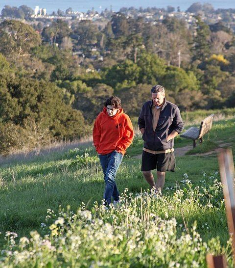 Nuori ja aikuinen kävelevät rinnakkain vihreällä mäenrinteellä. Taustalla näkyy äisesti kaupunkimaisema.