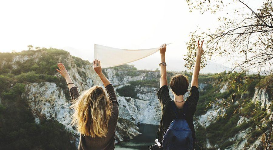 Kaksi naista seisoo selin kameraan ja pitävät valkoista kolmiolippua ylös ojennetuissa käsissään. Taustalla on vuorenrinne, jossa on lunta.
