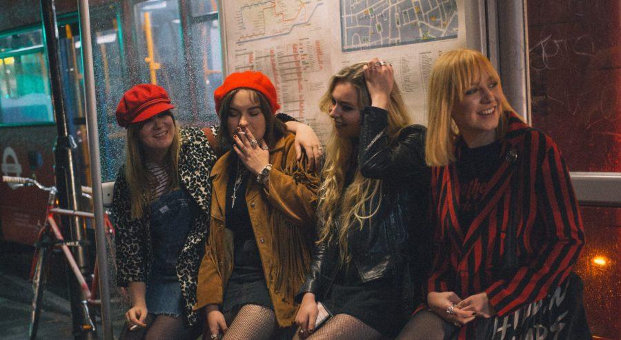 Nuoret naiset istuvat bussipysäkillä. Kuvassa on ilta. ja tytöt ovat juhlatuulella.