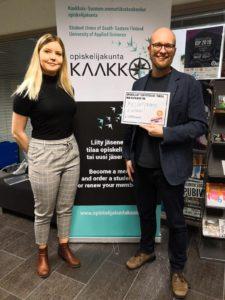 Iida Pilli-Sihvola ja Veli Liikanen poseravat Opiskelijakunta Kaakon roll up -mainoksen edessä.