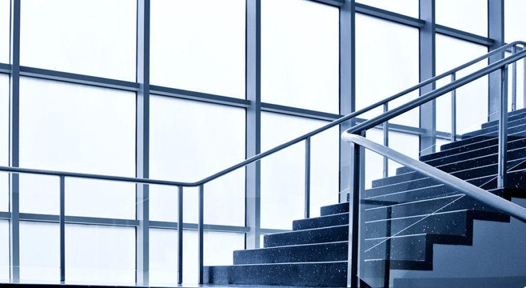 Kuva rakennusmuotoilusta. Lasiseinät ja raput valon kohdituessa niihin.