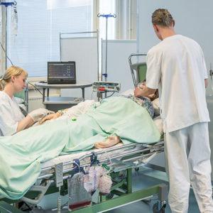 Kaksi opiskelijaa hoitavat sairaalasängyssä makaavaa simulaationukkea.