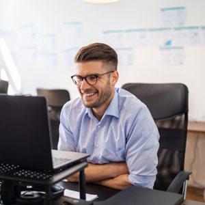 Mies katsoo tietokoneen näyttöä ja keskustelee jonkun kanssa.