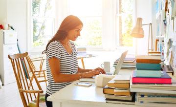 Nainen työskentelee kotonaan tietokoneen ääressä.