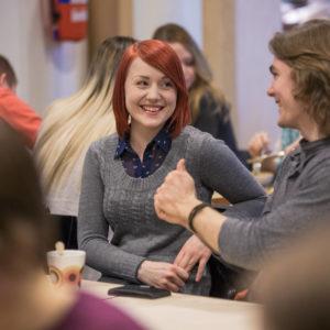 Tyttö ja poika istuvat pöydän ääressä keskustelemassa