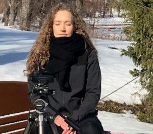 Nuori nainen talvimaisemassa pitämässä luentoja kameran takana.