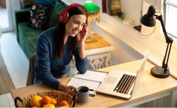Nainen katseleetietokoneen näyttöä, kahvikuppi kädessään.