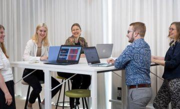 Opiskelijat ja henkilökunta keskustelevat pöydän ääressä iloisina.
